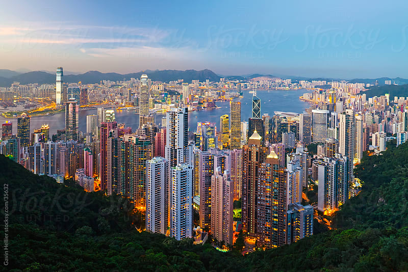 China, Hong Kong, Victoria Peak. View over Hong Kong from Victoria Peak. The illuminated skyline of Central sits below The Peak by Gavin Hellier for Stocksy United