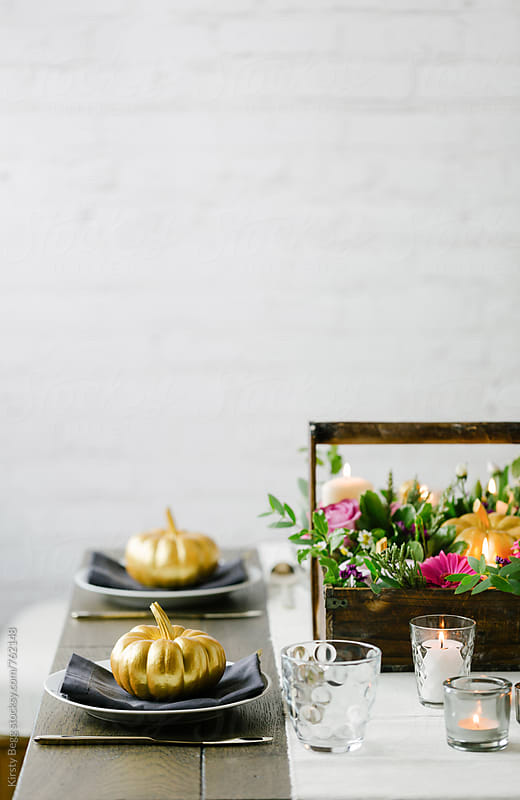Pumpkin and flower tablescape decor for Thanksgiving or Halloween by Kirsty Begg for Stocksy United