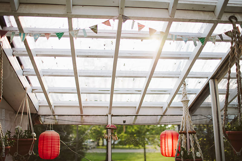 Lattice roof with sunshine coming through and red paper lanterns. by Sarah Lalone for Stocksy United