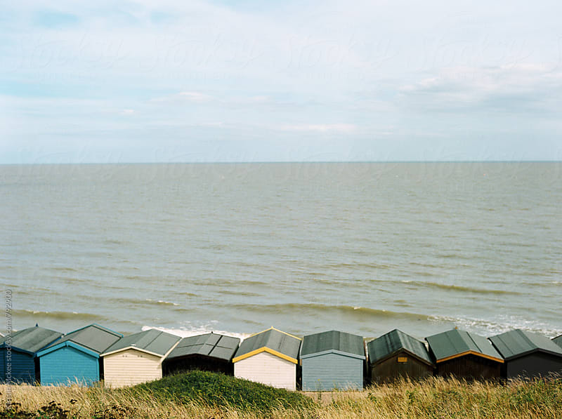 Row of beach huts with in the background in Frinton, Essex. by Kirstin Mckee for Stocksy United