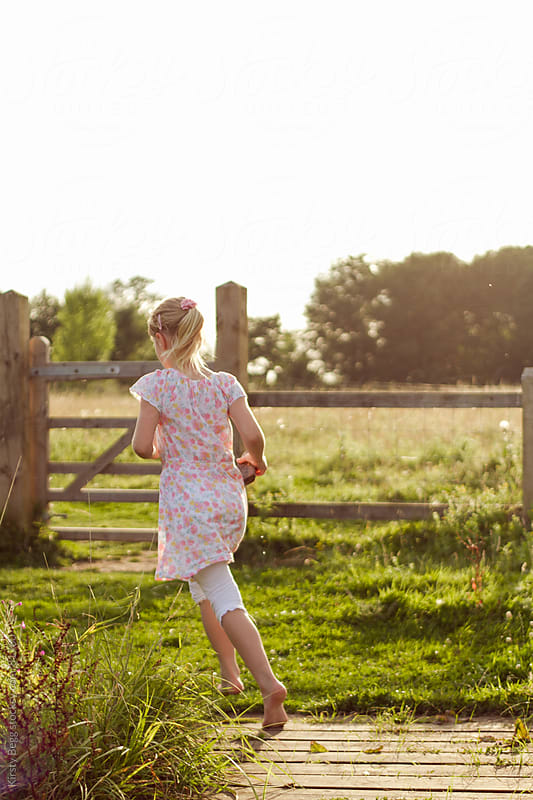Girl in evening light running on nature reserve boardwalk by Kirsty Begg for Stocksy United