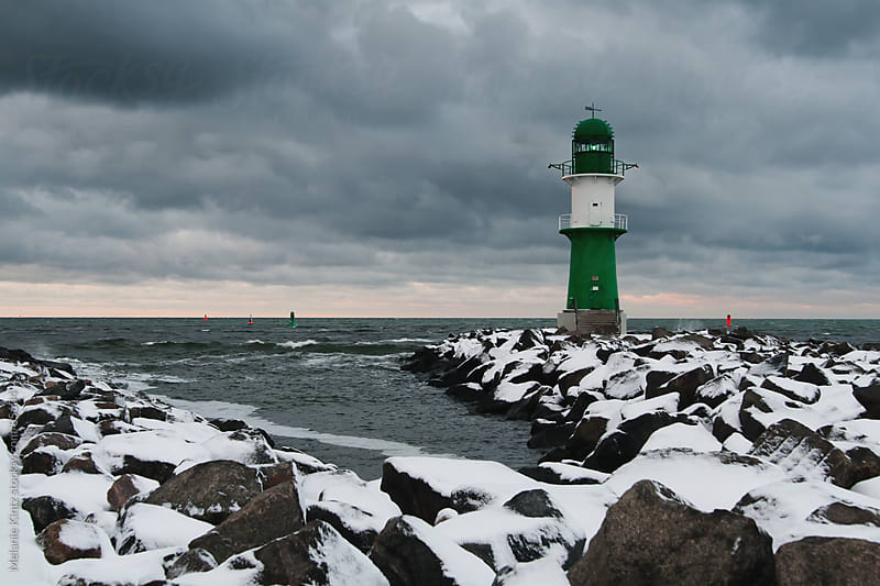 Lighthouse in winter at sunset by Melanie Kintz for Stocksy United