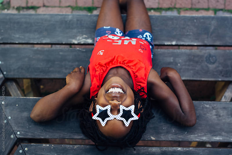 Smiling black girl in USA colors themed outfit by Gabriel (Gabi) Bucataru for Stocksy United