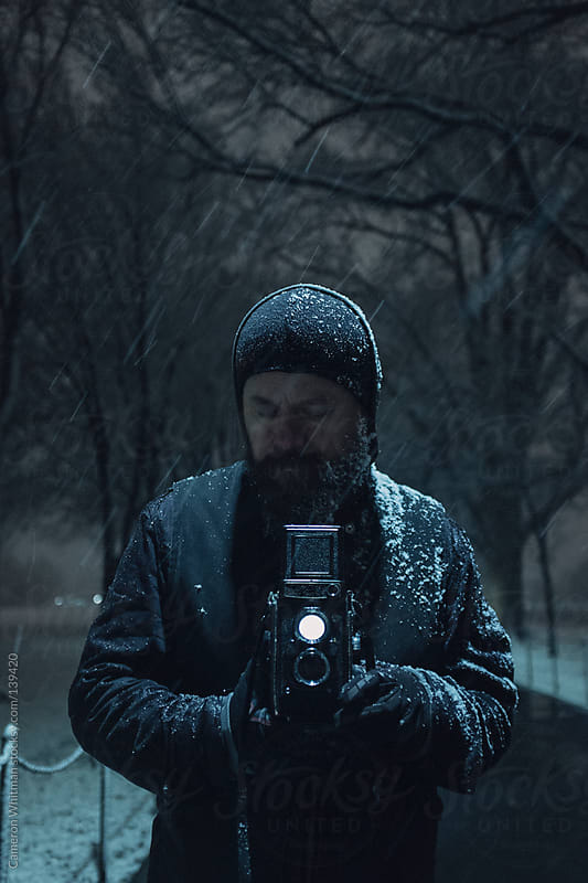 man photographing with a dual lens reflex camera in the snow by Cameron Whitman for Stocksy United