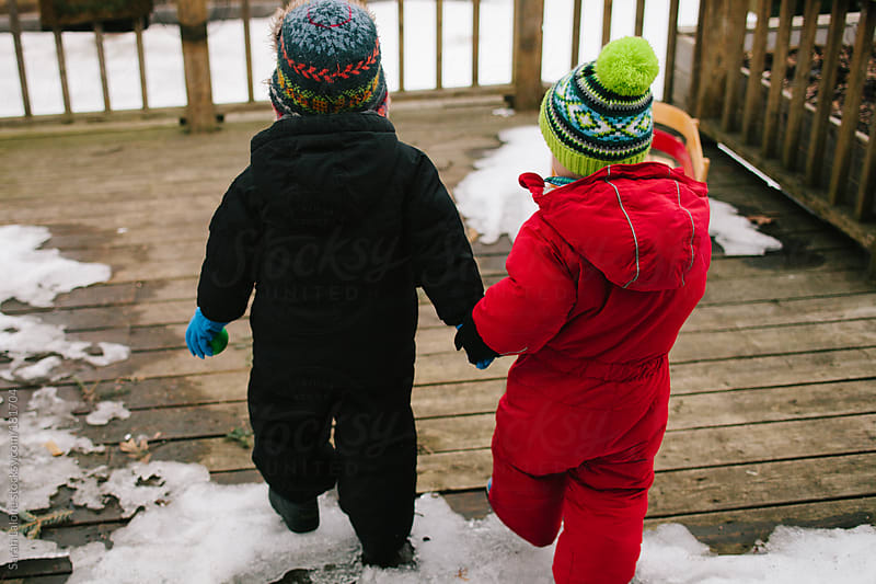 BFFs going out to play in the snow in their winter clothes by Sarah Lalone for Stocksy United
