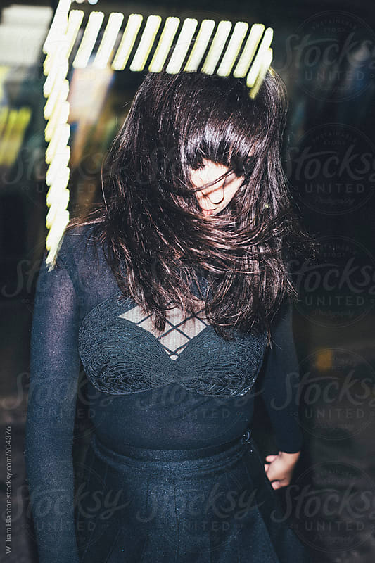 Woman fashion model wearing all black at night long exposed with flash by William Blanton for Stocksy United