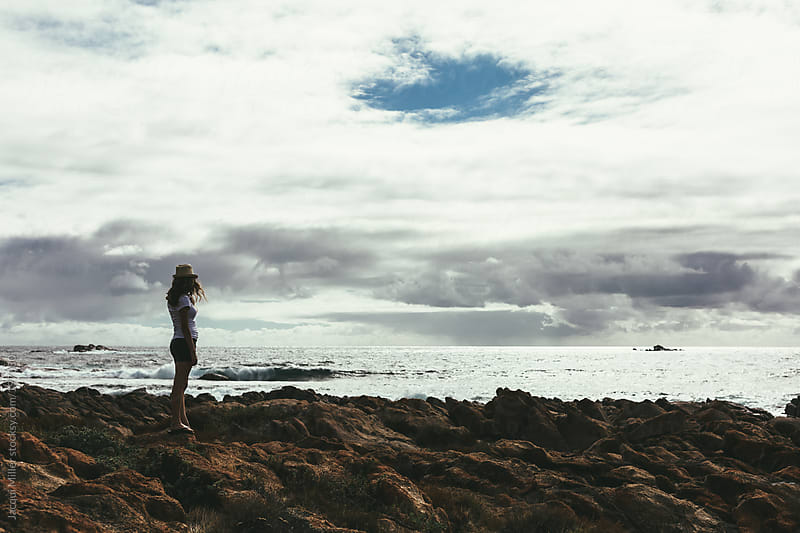 Teen girl standing on rocks looking at an overcast sky over the ocean by Jacqui Miller for Stocksy United
