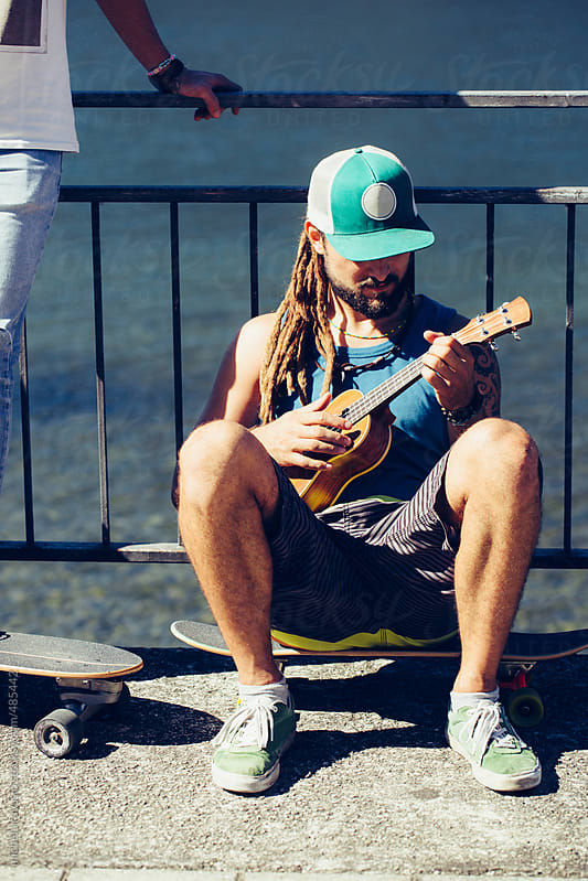 Young man playing ukelele by michela ravasio for Stocksy United