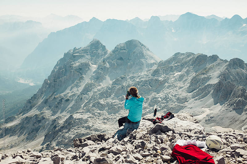 Mountaineer woman taking photos of the high mountains by Marko Milovanović for Stocksy United