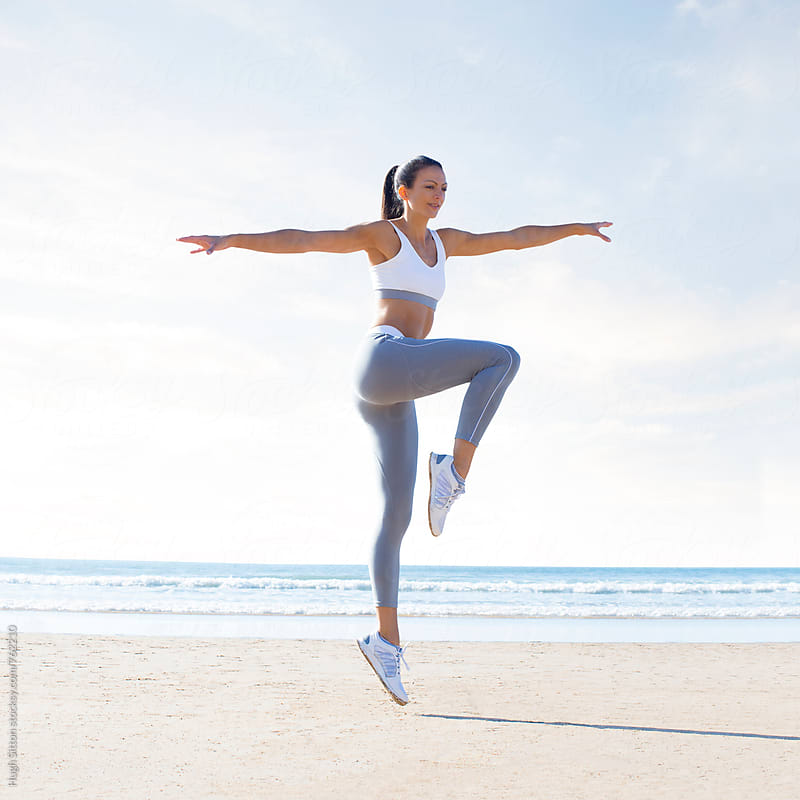 Professional female fitness trainer on beach. by Hugh Sitton for Stocksy United