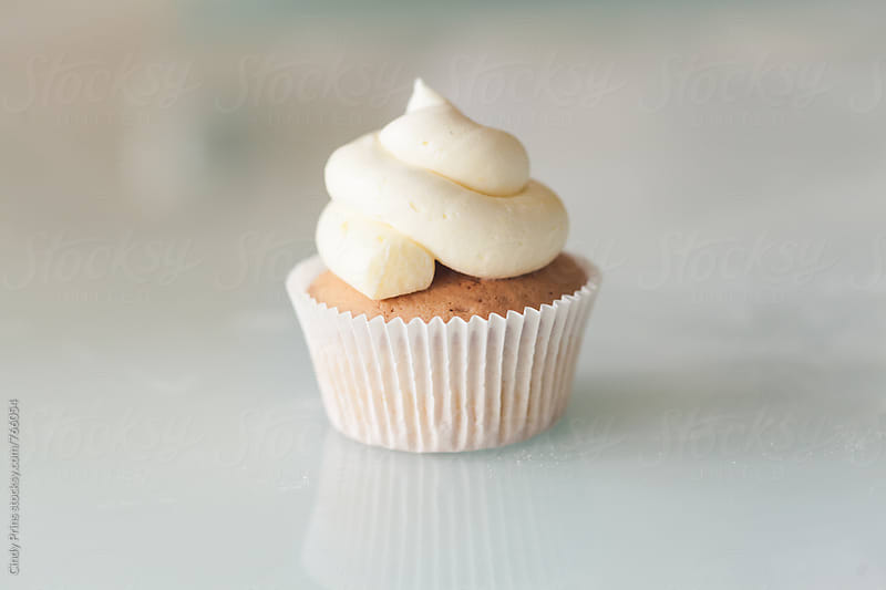 Closeup of a single vanilla cupcake on a white glass table by Cindy Prins for Stocksy United