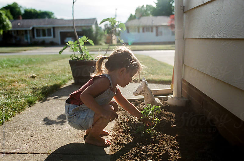 little girl planting garden by Maria Manco for Stocksy United