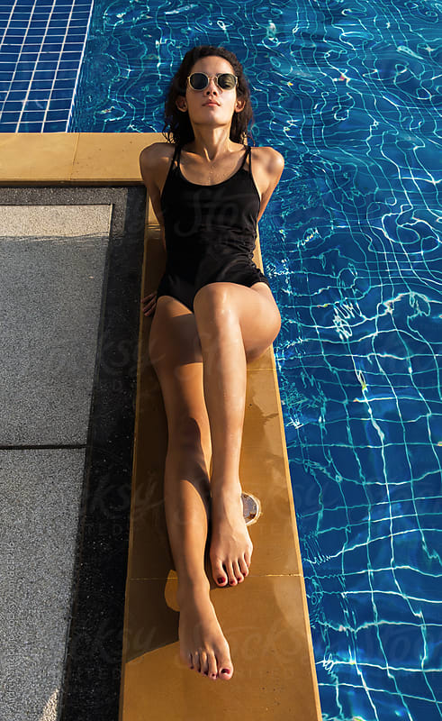 Portrait of beautiful young woman sunbathing next to pool. by Audrey Shtecinjo for Stocksy United