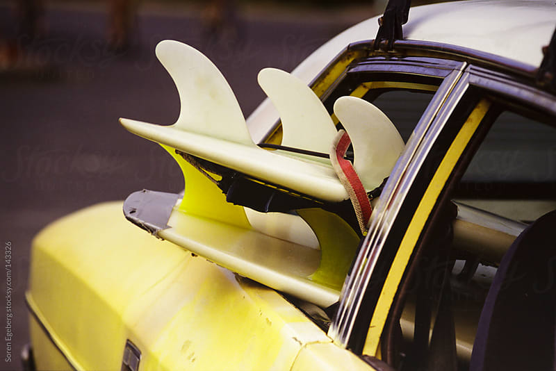 Surf boards sticking out of the window of an old car. by Soren Egeberg for Stocksy United