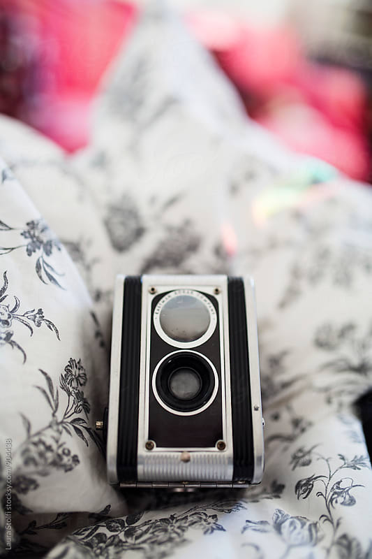 Twin lens reflex on bed with rainbow by Laura Stolfi for Stocksy United