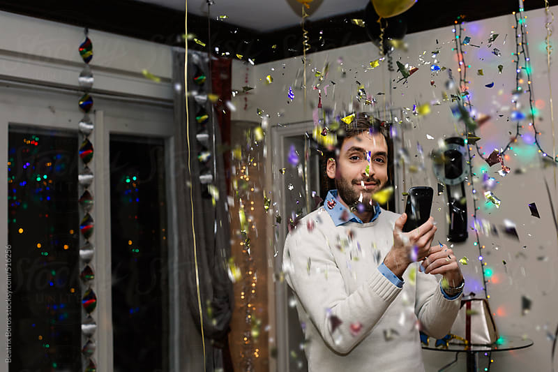 Man holding his cellphone and looking at camera while confetti falling at a party by Beatrix Boros for Stocksy United