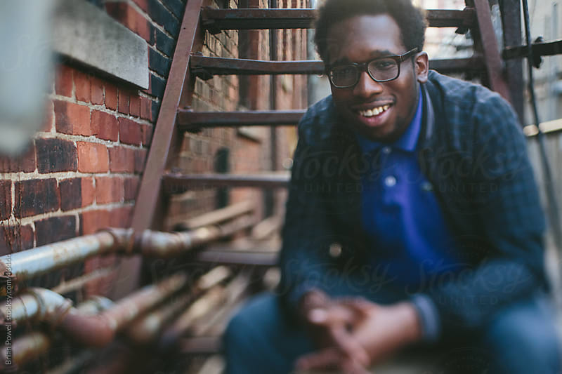 young Black man smiling (freelensed)  by Brian Powell for Stocksy United