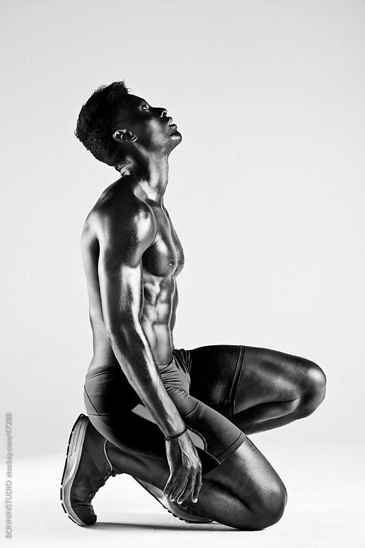 Sprinter african muscular man in total concentration by BONNINSTUDIO for Stocksy United