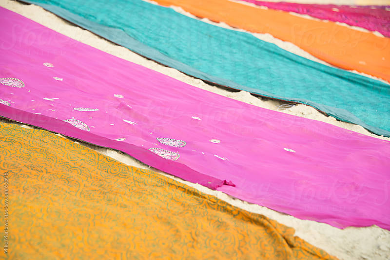 Bright colored saris laid out on sand. by Mike Marlowe for Stocksy United