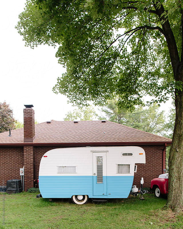 vintage camper parked by house by Brian Powell for Stocksy United
