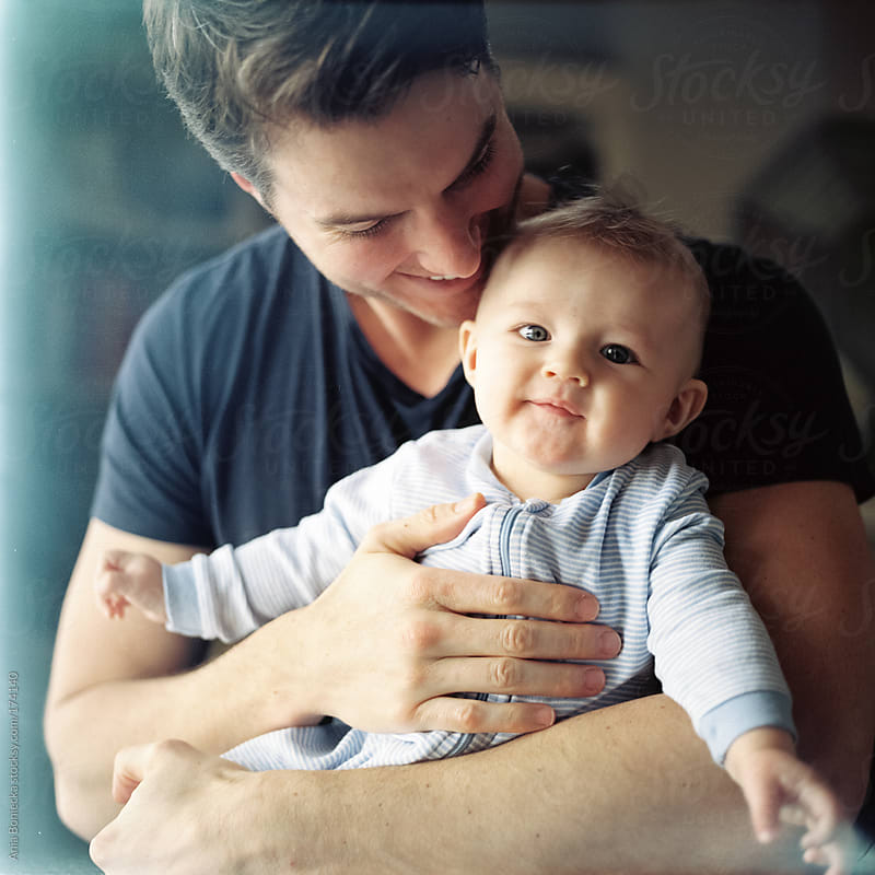 Happy father holding baby son in his arms by Ania Boniecka for Stocksy United