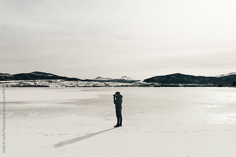 Photographer shooting a photograph on a frozen lake by Isaiah & Taylor Photography for Stocksy United