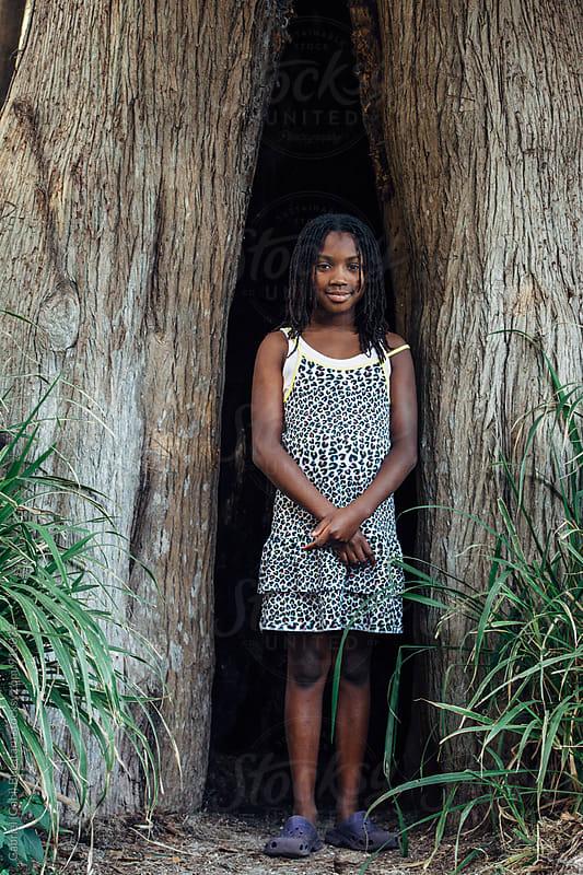 Cute black girl in a tree hollow by Gabriel (Gabi) Bucataru for Stocksy United