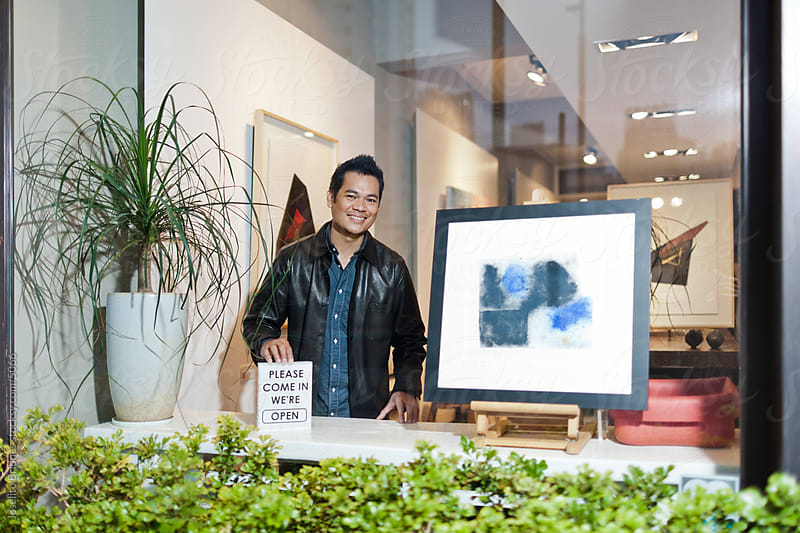Small Art Gallery Owner Holding Open for Business Sign by Joselito Briones for Stocksy United