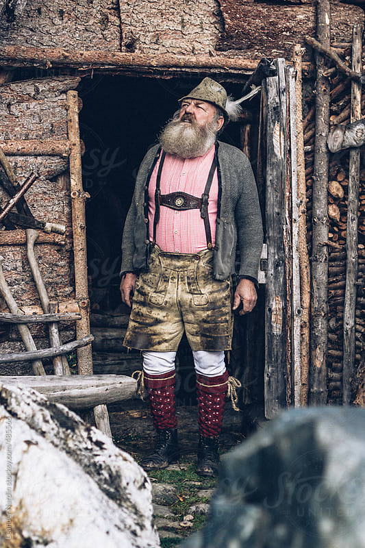old bearded man in typical austrian outfit looking out of a wooden cabin by Leander Nardin for Stocksy United