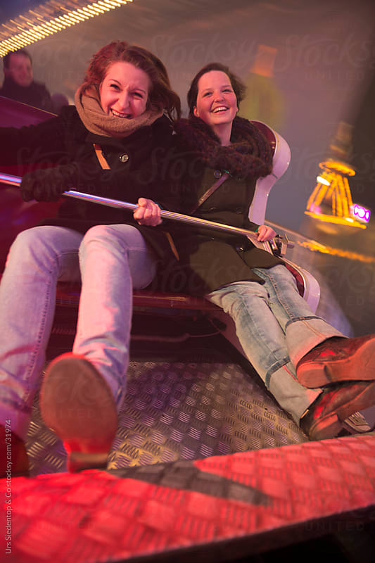 Two young women in fairground ride having fun by Urs Siedentop & Co for Stocksy United