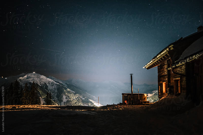 wooden alpine cabin with jacuzzi in snowcovered mountain landscape at night under starry sky by Leander Nardin for Stocksy United