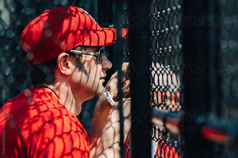 Baseball coach in red shirt and cap looking through a wire fence by Gabriel (Gabi) Bucataru for Stocksy United