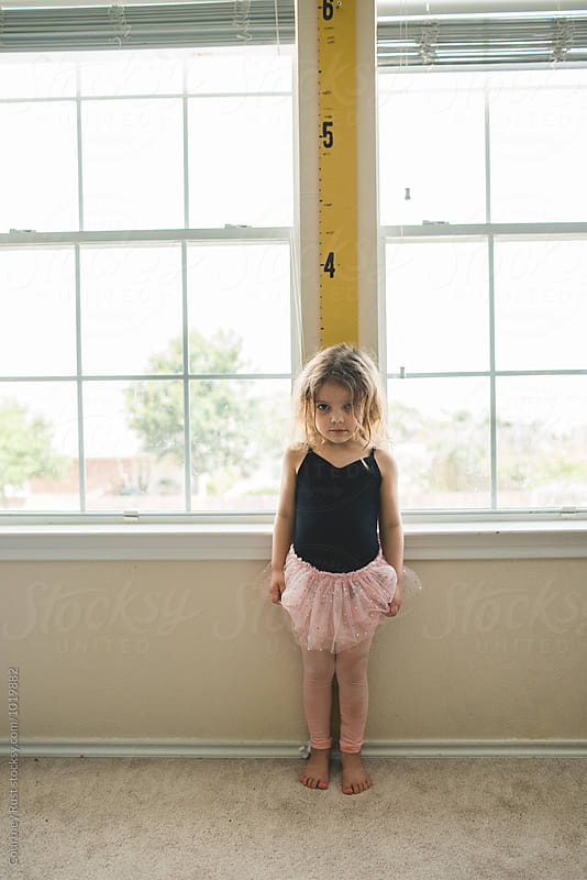 Child in a tutu being measured on a keepsake measuring stick  by Courtney Rust for Stocksy United
