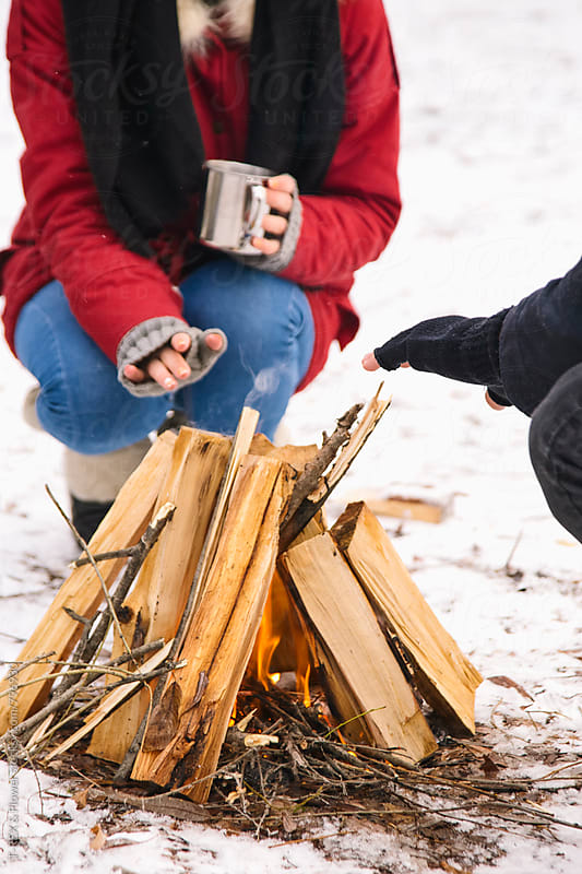 Close-up of couple warming themselves at fire by Danil Nevsky for Stocksy United