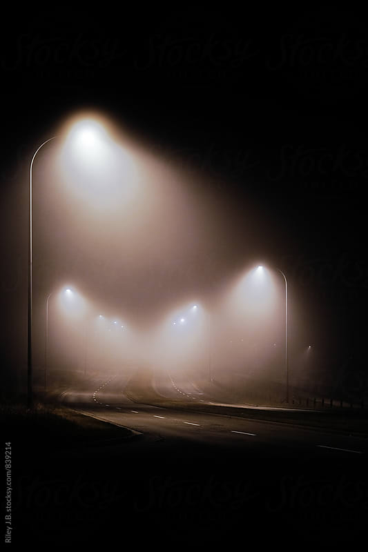 An empty, winding road on a foggy night by Riley Joseph for Stocksy United