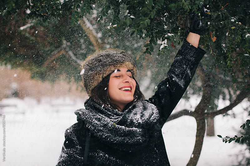 Happy woman having fun in the park on a snowy day by VeaVea for Stocksy United