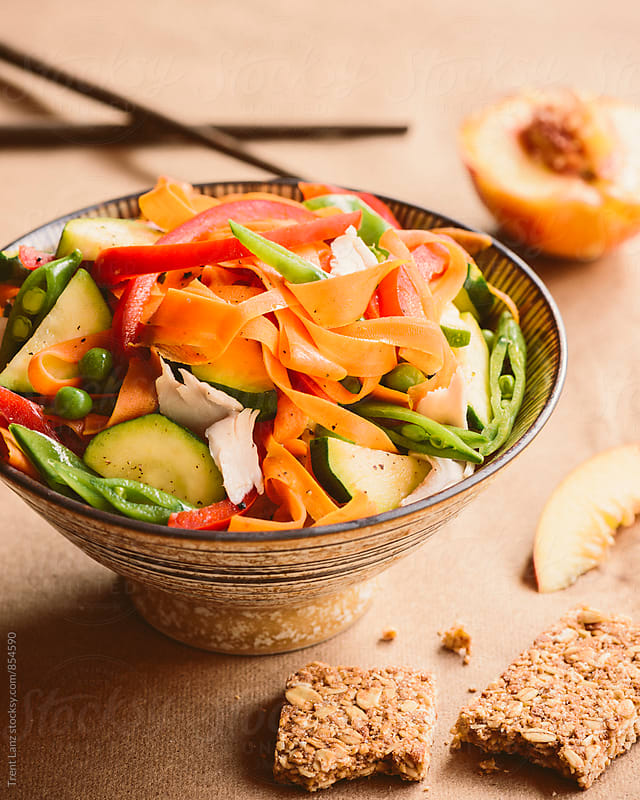 Fresh Asian salad with nectarine and granola bar by Trent Lanz for Stocksy United