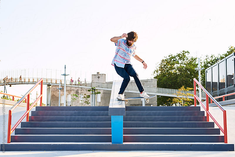 Hairy skateboarder performing trick on steps by Guille Faingold for Stocksy United