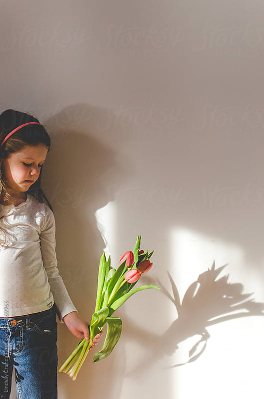 Young girl holding tulips in sunlight by Lindsay Crandall for Stocksy United