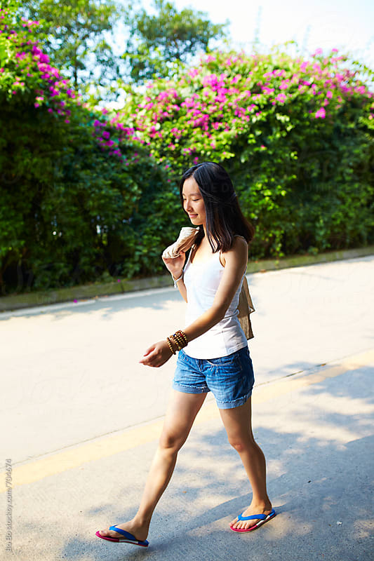 young asian woman walking in the summer road by Bo Bo for Stocksy United