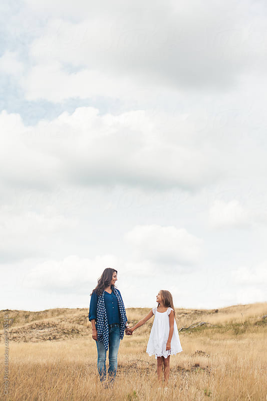 Mother and daughter standing in a golden field underneath a big cloudy sky by Cindy Prins for Stocksy United