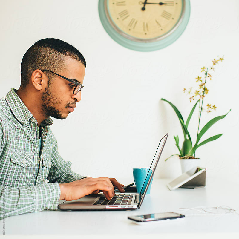Young professional man using laptop by michela ravasio for Stocksy United