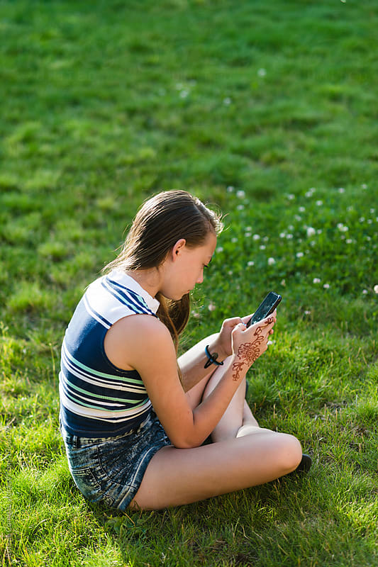 Teenage Girl Using Electronic Device While Outdoors by Ronnie Comeau for Stocksy United