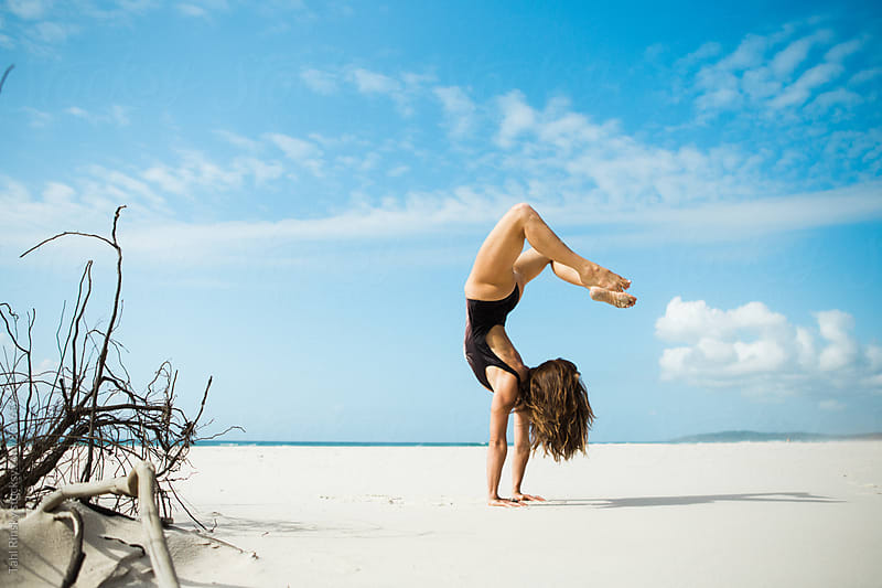 women balancing in scorpion handstand on empty beach  by Tahl Rinsky for Stocksy United