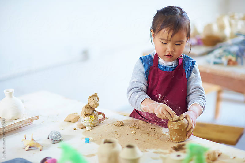 lovely little asian girl busy in the pottery by cuiyan Liu for Stocksy United