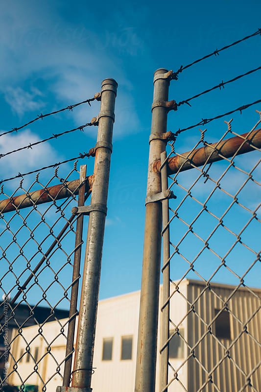 Detail of barbed wire and chain-link fence, warehouse in distance by Paul Edmondson for Stocksy United