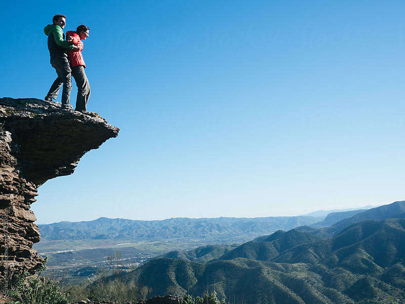 Couple standing on a cliff with el chorro landscape below by Martin Matej for Stocksy United