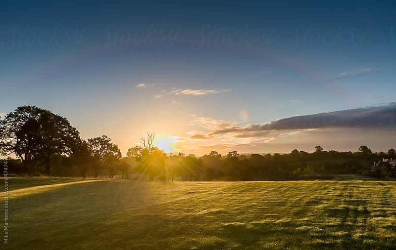 Sunrise over a green field. by Mike Marlowe for Stocksy United