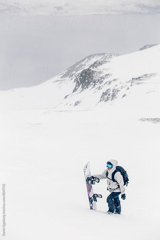 Female snowboarder walking uphill in the snow with snowboard by Soren Egeberg for Stocksy United
