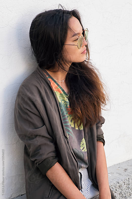 Pensive Asian girl in glasses looking away by Danil Nevsky for Stocksy United